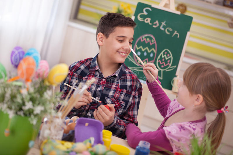 Happy young boy and girl playing with Easter eggs. Two smiling kids paint easter eggs royalty free stock photo