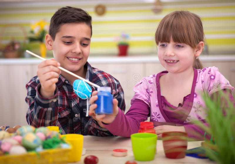 Happy young boy and girl playing with Easter eggs. Two smiling kids paint easter eggs stock image