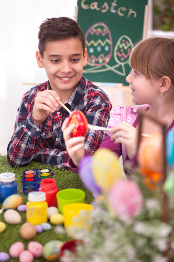 Happy young boy and girl playing with Easter eggs. Two smiling kids paint easter eggs royalty free stock photos