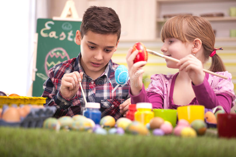 Happy young boy and girl playing with Easter eggs. Two smiling kids paint easter eggs stock photo