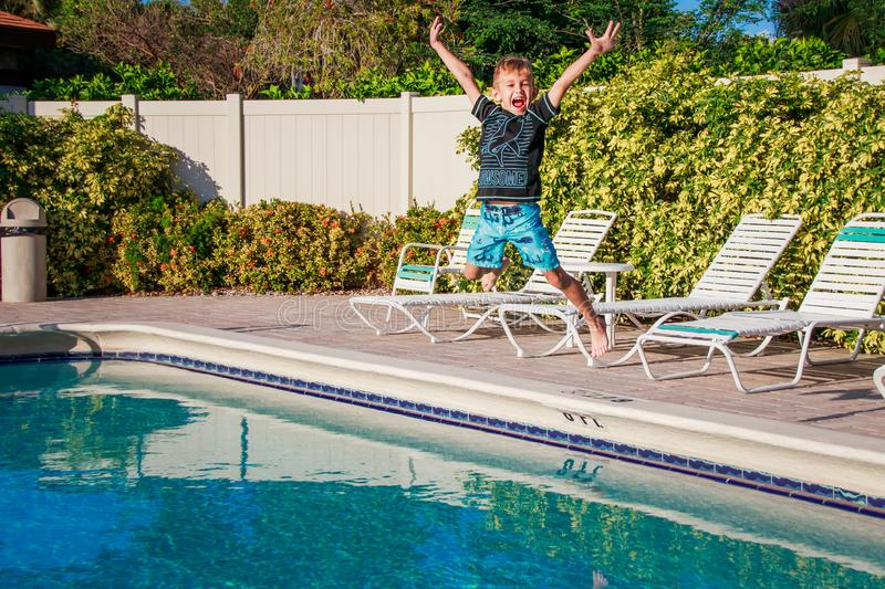 Happy young boy jumping to the pool water in golden hours time royalty free stock photos