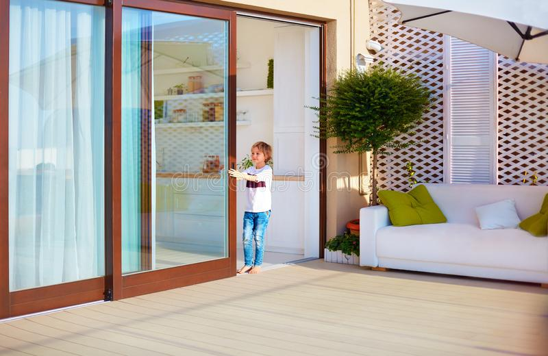 Happy young boy, kid opening the sliding door on rooftop patio area at home royalty free stock photos