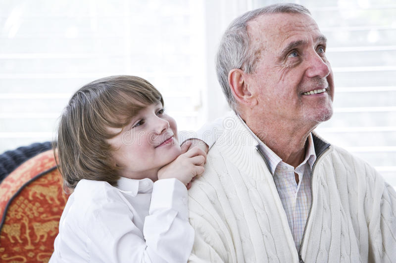 Happy young boy leaning on shoulder of grandfather. Looking up royalty free stock photo