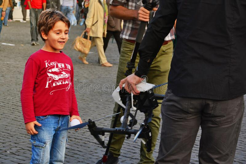 Happy young boy looks with admiration at a drone in the hand of a drone pilot stock photography
