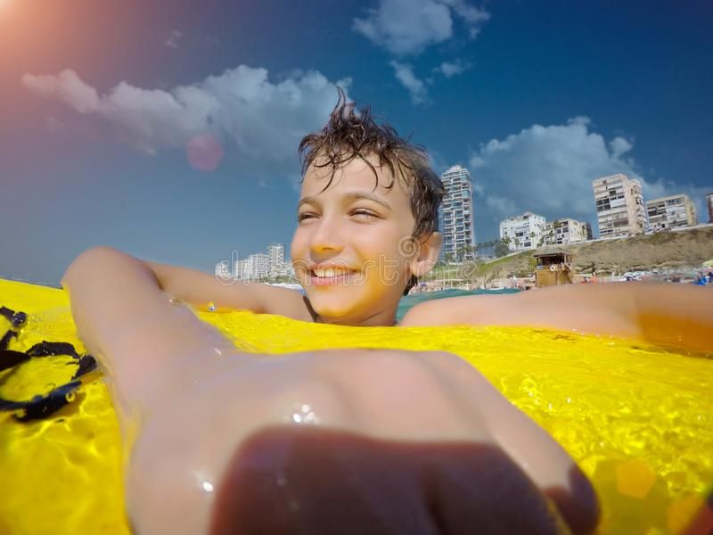 Happy young boy in the ocean on surfboard stock photo
