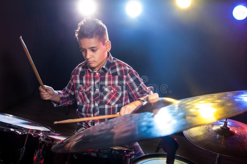 Young boy playing drums. Happy young boy playing drums stock photography