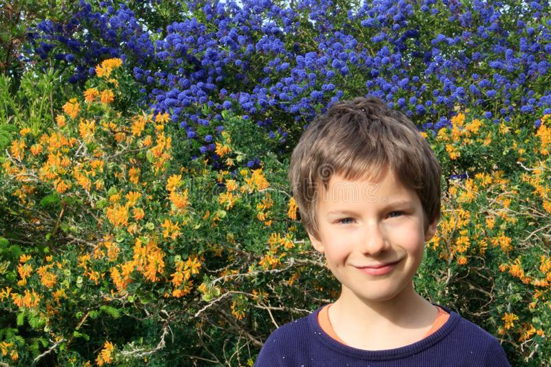 A happy young boy portrait outdoor in the spring garden. Children gardening design. Floral background stock images
