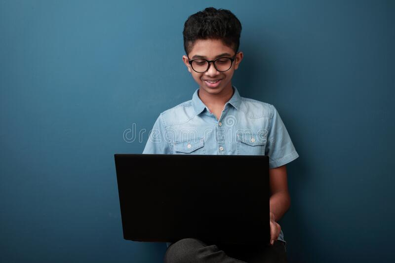 Smiling young boy with laptop stock image