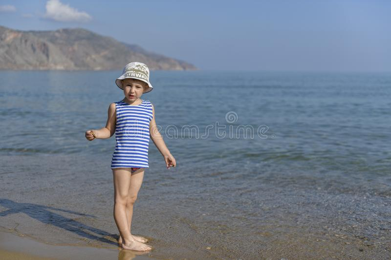 Boy in striped t-shirt on the beach stock image