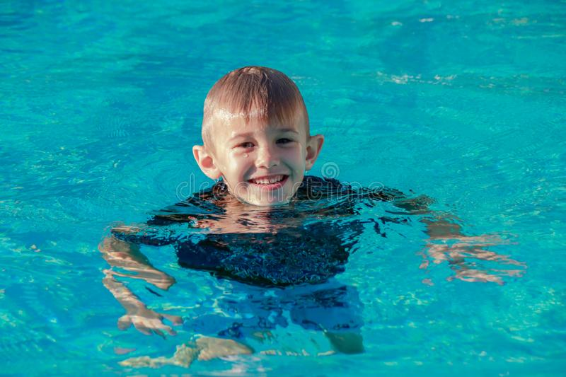 Happy young boy swimming in a pool outdoor. In South Florida royalty free stock photos