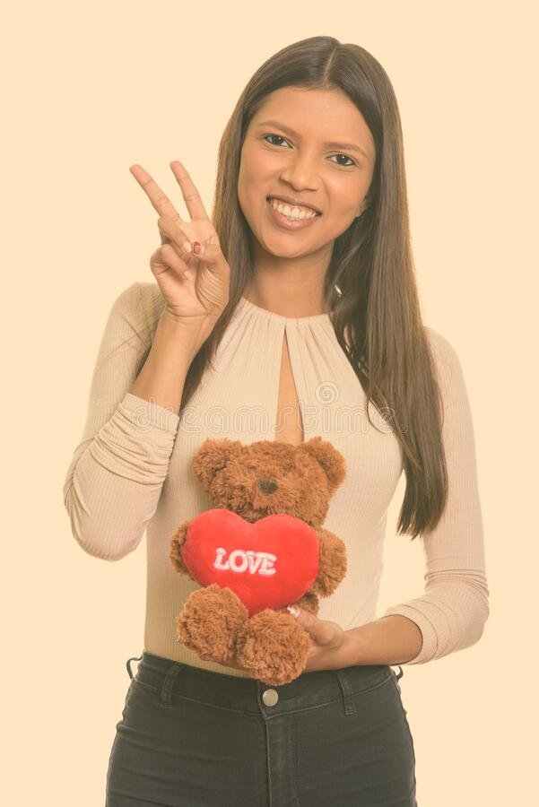 Happy young Brazilian woman giving peace sign while holding teddy bear. Studio shot of young beautiful Brazilian woman isolated against white background stock images