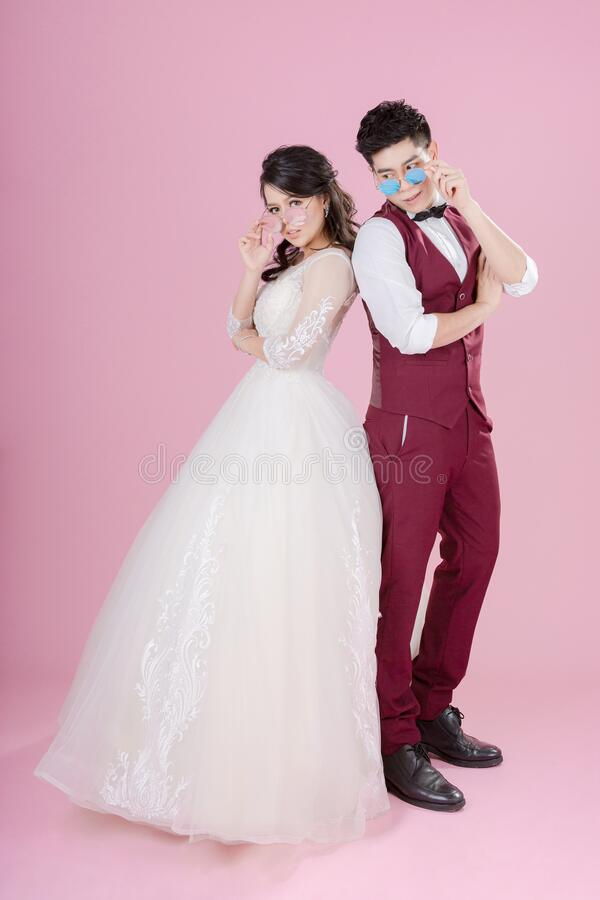 Free Happy Young Bride And Groom Wearing Sunglasses On The Pink Background. Wedding Couple, New Family, Wedding Dress. Bridal Wedding. Royalty Free Stock Photo - 169407275
