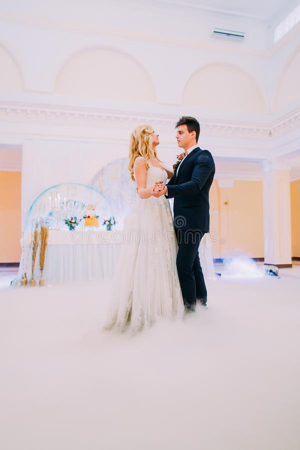 Happy young bride and groom dance in the wedding hall stock images