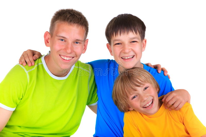 Happy young brothers. Portrait of three happy young brothers of different ages wearing colorful clothing, white background stock images