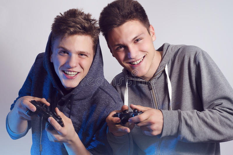Happy young brothers playing video games, selective focus on faces stock photos