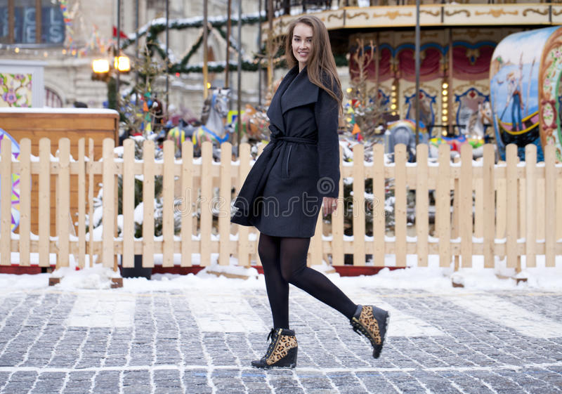 Happy young brown haired woman on the background of a winter amusement park royalty free stock image