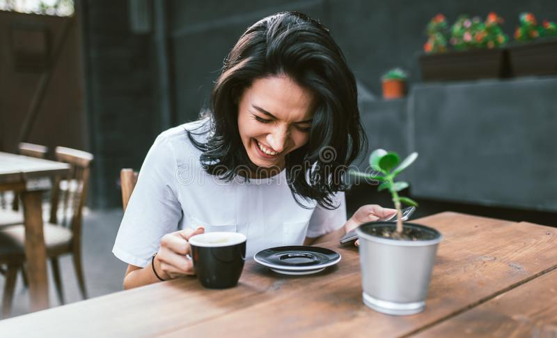Happy young brunette female student with laughing and siting in modern cafe interior, using cell phone, checking newsfeed on her royalty free stock photography