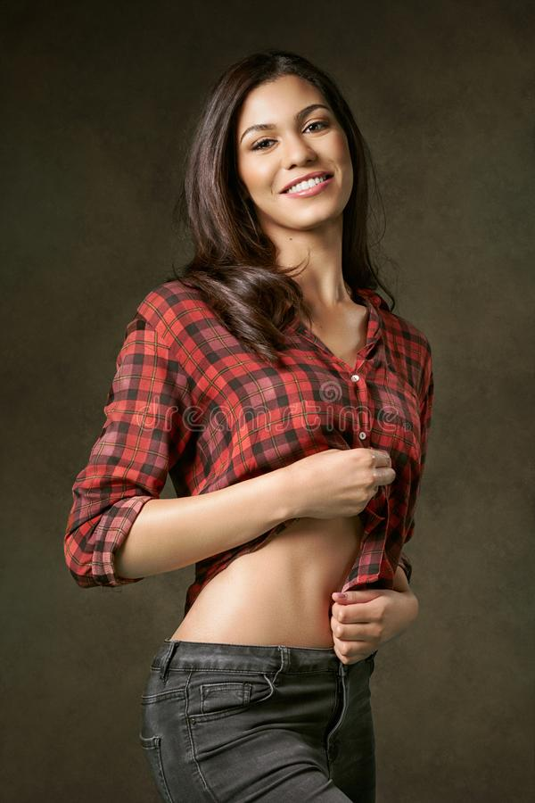 Young, attractive, smiling woman in a red plaid shirt. stock photography