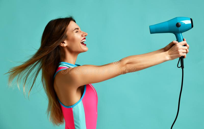 Happy young brunette woman with hair dryer on blue mint background royalty free stock images