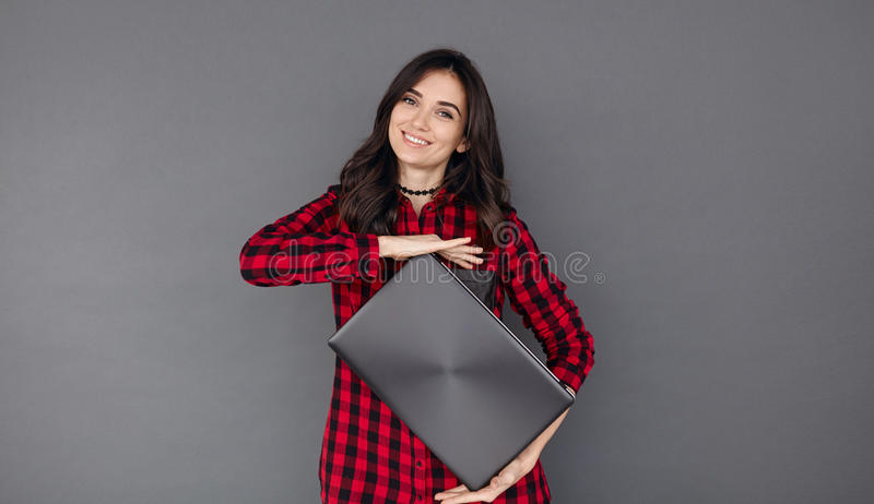 Happy young brunette woman holding a laptop royalty free stock photos