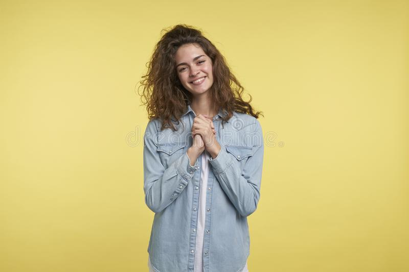 Happy young brunette woman, keeps palms together, isolated over yellow background royalty free stock image