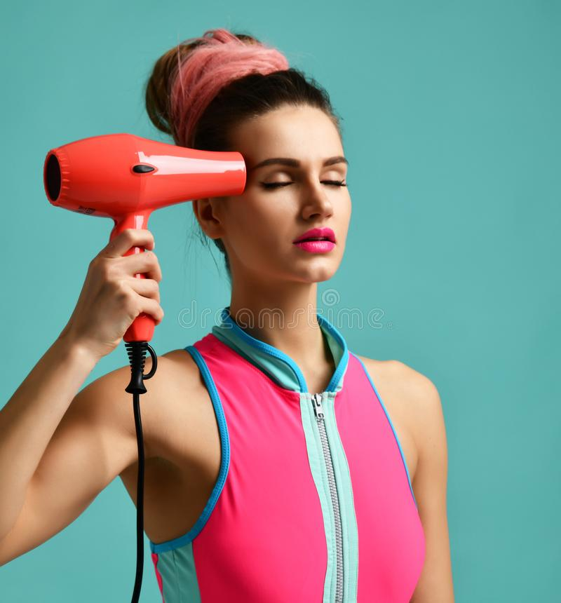 Happy young brunette woman with red hair dryer on blue mint background stock images
