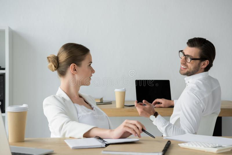 Happy young business colleagues chatting at workplace. In office stock photo