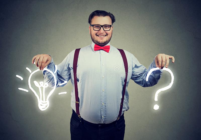 Happy young business man with question and an answer idea light bulb. On gray wall background stock images