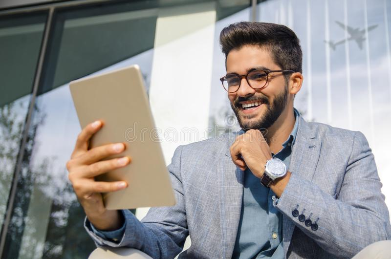 Happy young business man sitting outside of the airportground stock image