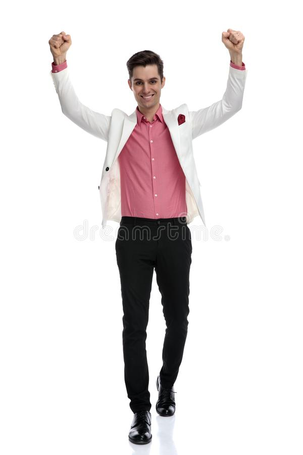 Happy young business man walking with hands in the air stock photos