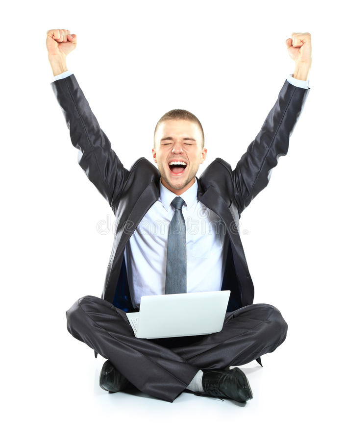 Happy young business man working on a laptop stock photography