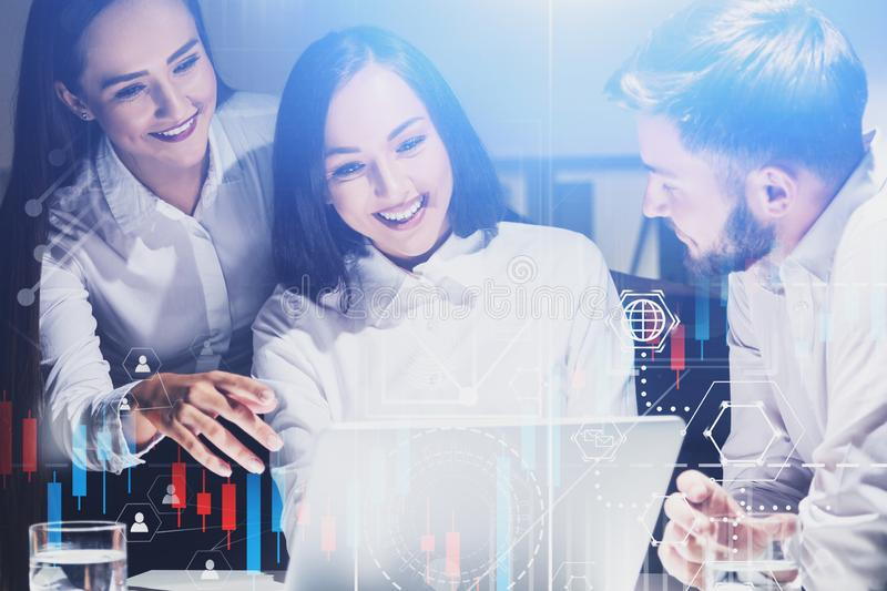 Happy young business people in office, graphs. Cheerful young business people working in office with laptop and double exposure of graphs and business interface stock photo