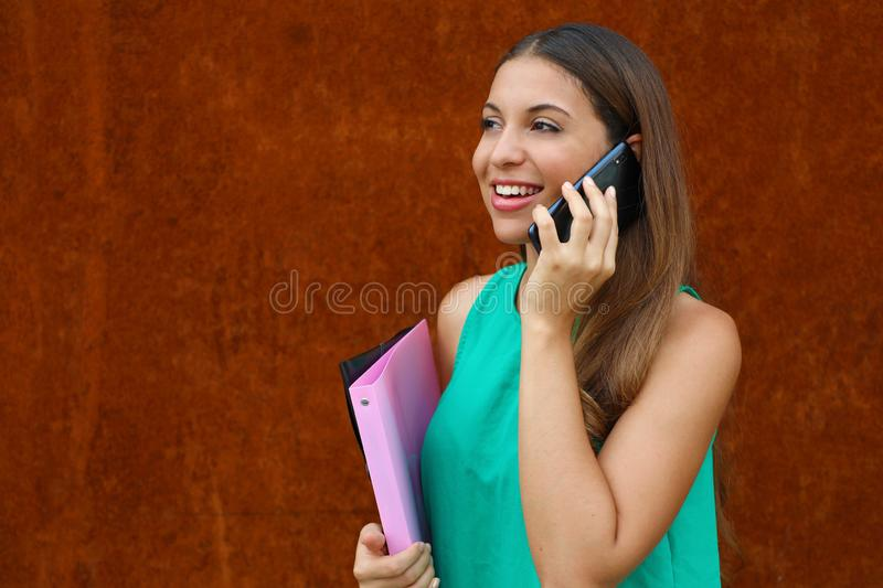 Happy young business woman calling with phone on rust background. Copy space stock images