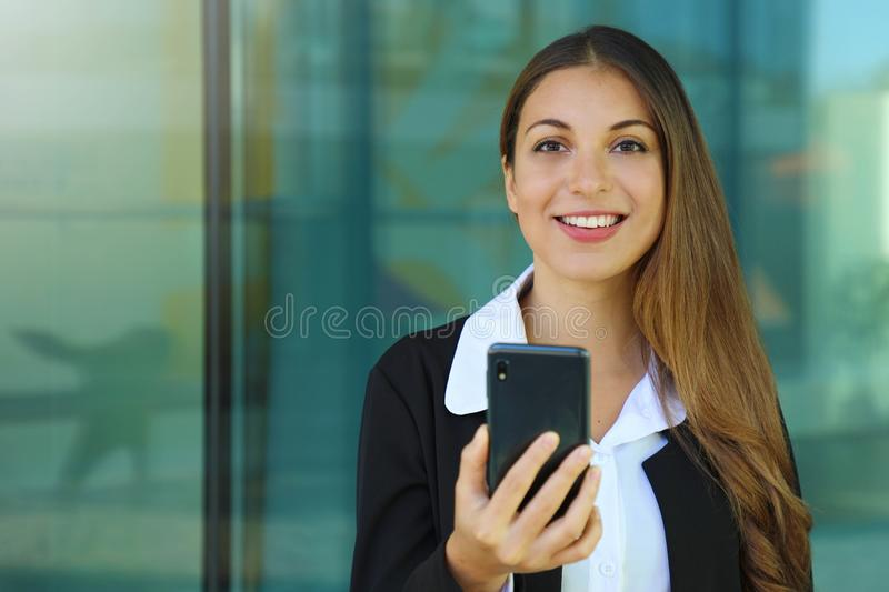 Happy young business woman checking her smart phone and looking at camera out of office. Copy space royalty free stock photos