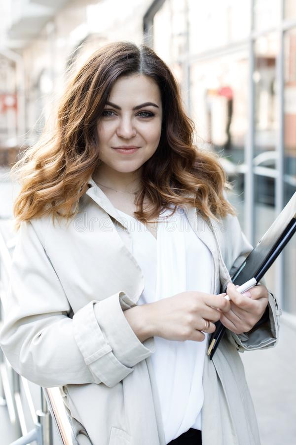 A young, sympathetic woman, not a thin-headed body building, holds a folder of paper in her hands. Happy young business woman with stock images