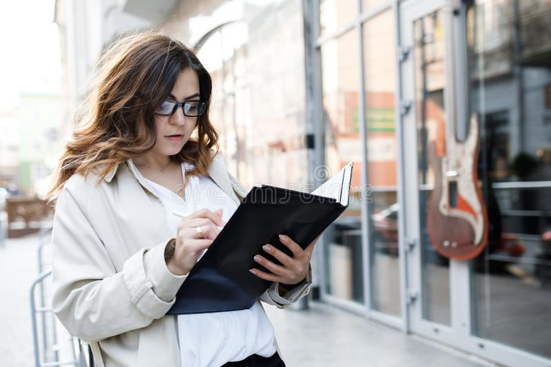 A young, sympathetic woman, not a thin-headed body building, holds a folder of paper in her hands. Happy young business woman with stock photography