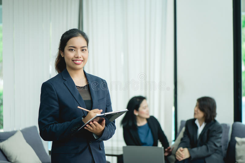 Happy young business woman with her staff, people group in background at modern bright office indoors stock images