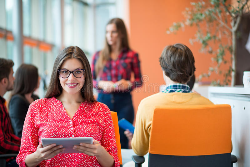 Happy young business woman with her staff, people group in background at modern bright office indoors. Happy young business women with her staff, people group in royalty free stock images