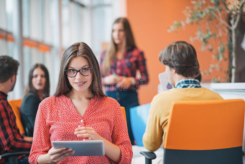 Happy young business woman with her staff, people group in background at modern bright office indoors royalty free stock images