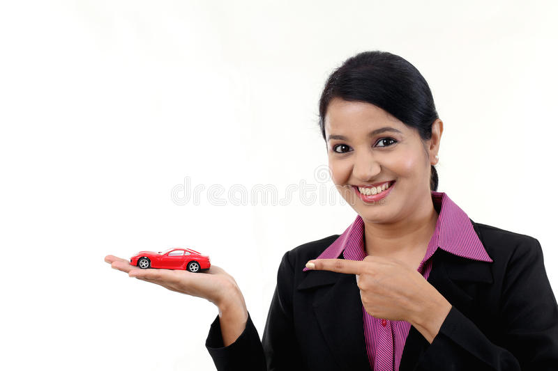 Happy young business woman holding toy car stock photography