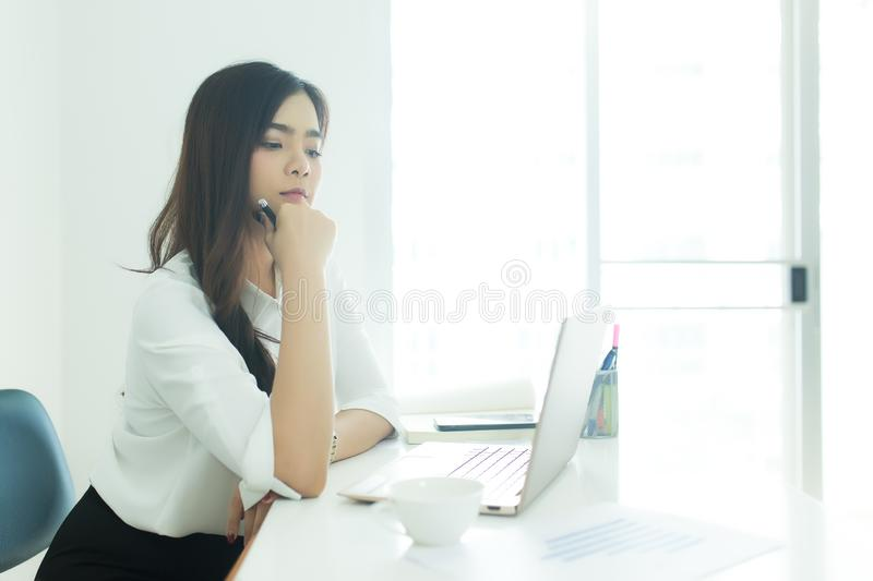 Happy young business woman looking at her laptop in modern office. working concept. stock image