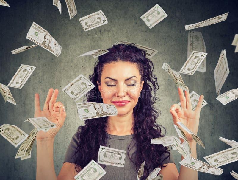 Woman meditating under money rain royalty free stock photos