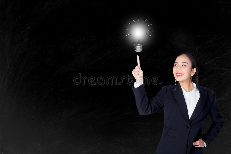 Happy young business woman pointing light bulb with inspiration and idea concept. royalty free stock photos