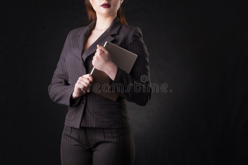 Happy young business woman posing over dark wall background. royalty free stock photos