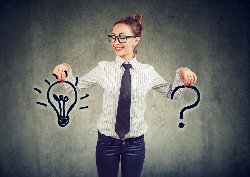 Happy young business woman with question and an answer idea light bulb. On gray wall background stock image
