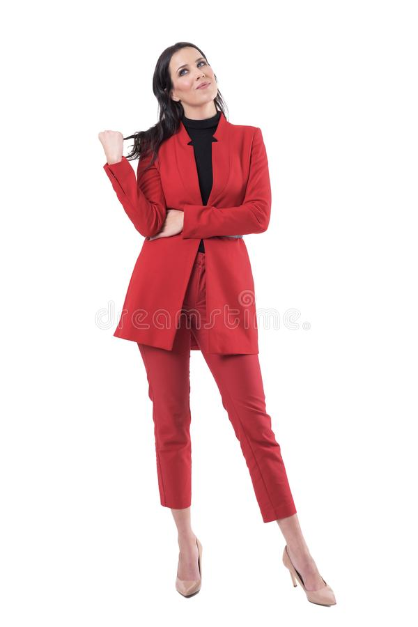 Happy young business woman in red suit touching hair thinking and looking up having idea. Full body isolated on white background royalty free stock image