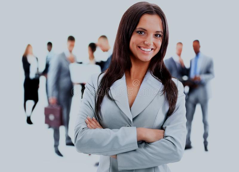 Happy young business woman standing in front of her team. stock photos