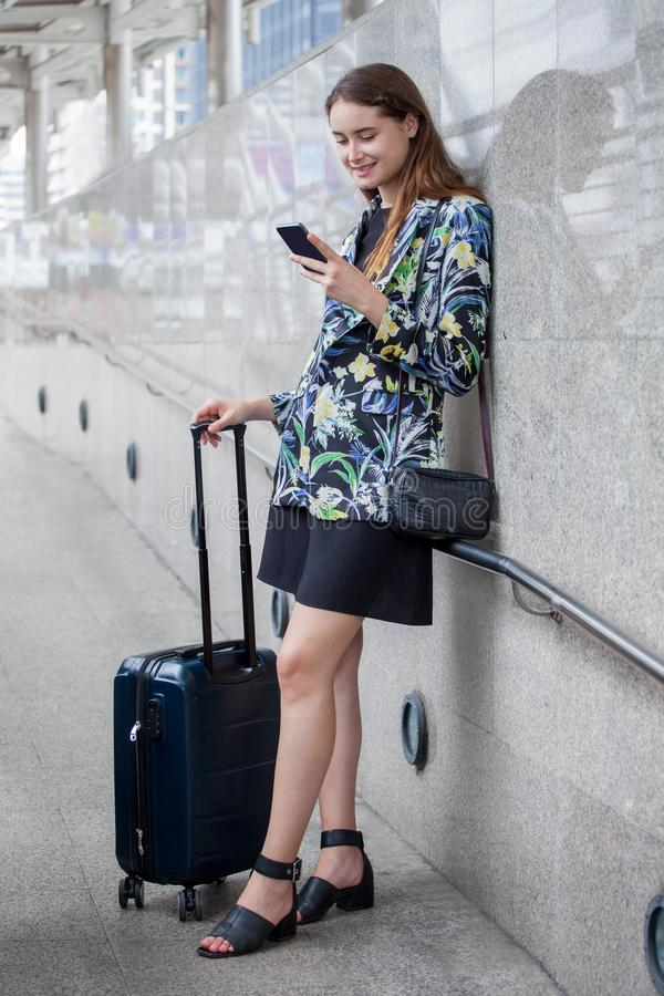 Happy young business woman standing with hand luggage using mobile phone . traveling girl with suitcase and  smartphone in city. Outdoors woman airport royalty free stock image