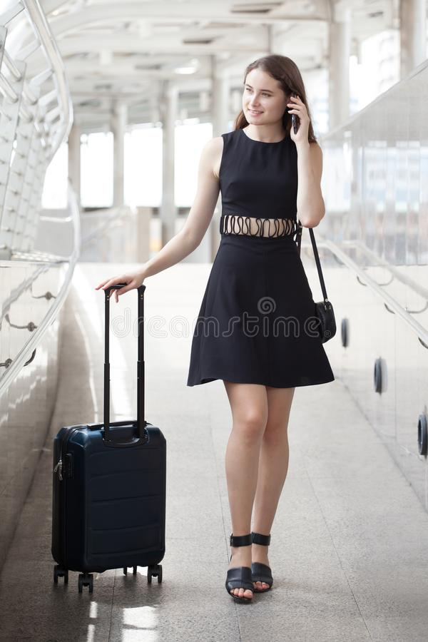 happy young business woman walking and carrying hand luggage using mobile phone . traveling girl with suitcase and  smartphone in royalty free stock image