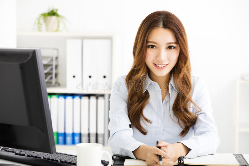 Happy young business woman working in office royalty free stock image